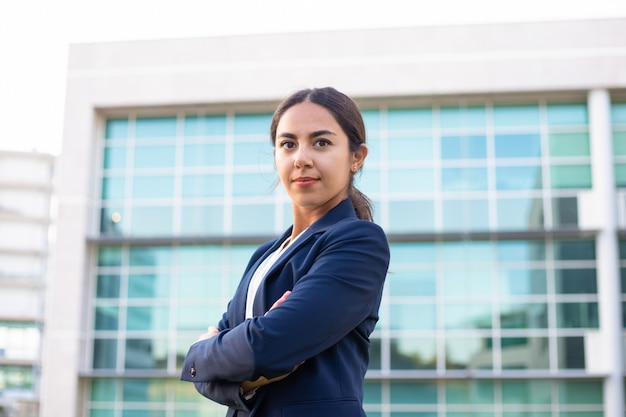 Confident young businesswoman standing with crossed arms