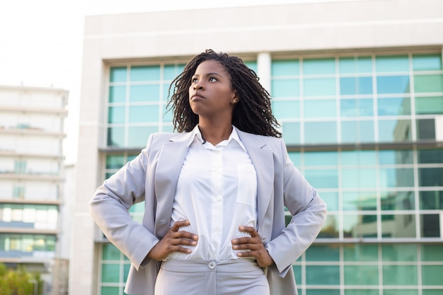 Confident young businesswoman with hands on waist