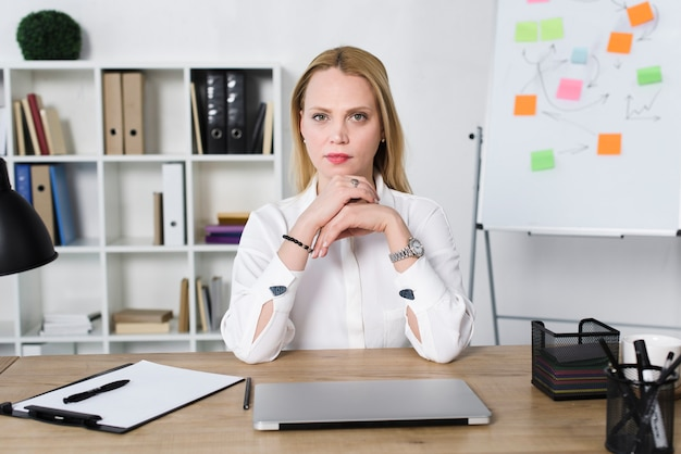 Confident young businesswoman with laptop on table in the office