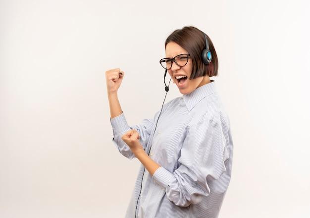 Уверенная молодая девушка call-центра в очках и гарнитуре, стоящая в профиле, жестикулирует, изолирована на белом с копией пространства
