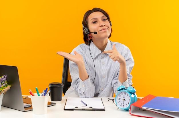 机に座って空の手を示し、オレンジ色に分離されたそれを指しているヘッドセットを身に着けている自信を持って若いコールセンターの女の子