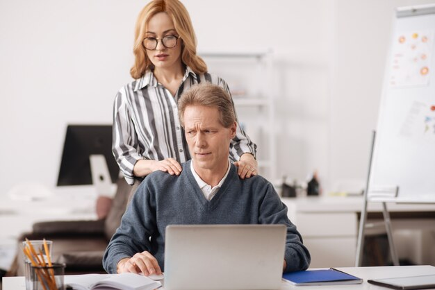 彼に触れて誘惑しながら同僚の後ろのオフィスに立っている自信を持って若い慎重な実業家