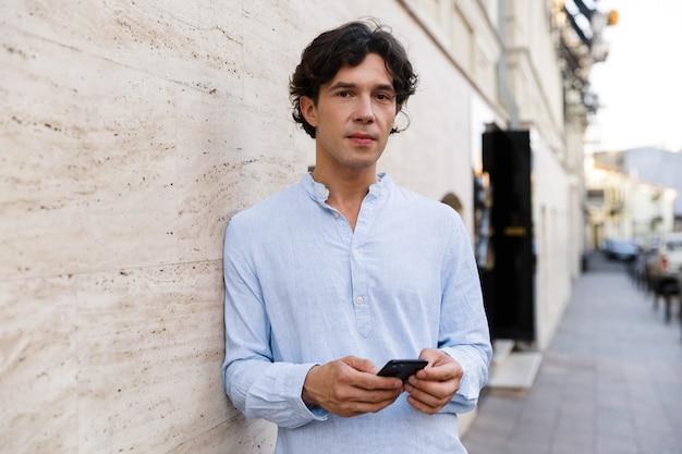 Уверенный молодой случайный человек, держащий мобильный телефон