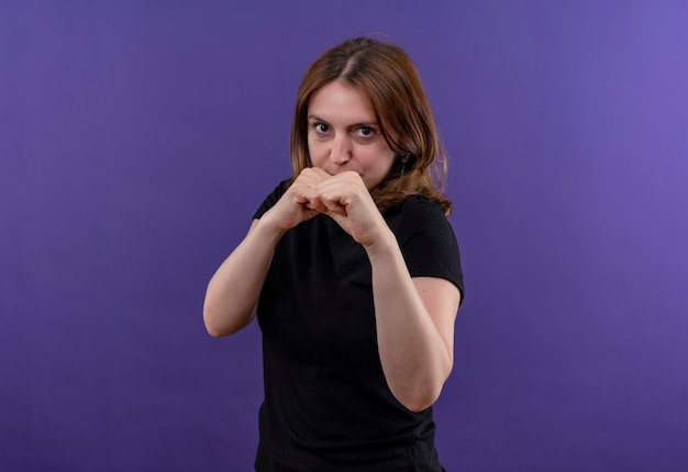 Confident young casual woman doing boxing gesture on isolated purple space with copy space