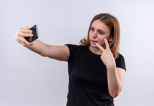 Confident young casual woman doing peace sign and taking selfie on isolated white space