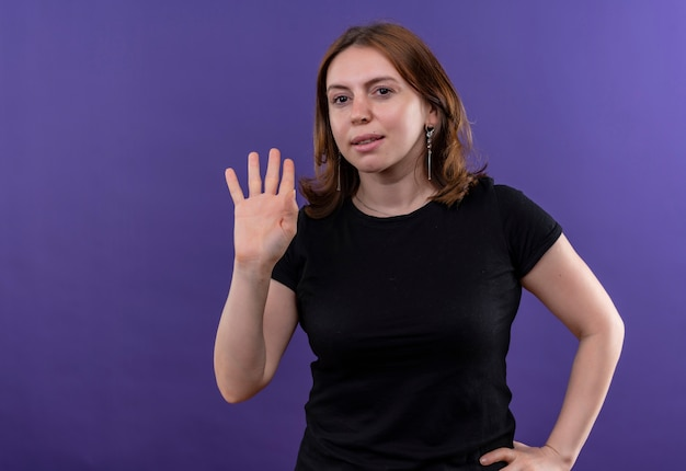 Confident young casual woman gesturing hi with hand on waist on isolated purple space with copy space