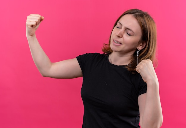 Confident young casual woman gesturing strong with raised fists and closed eyes on isolated pink space