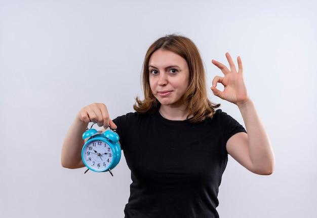 目覚まし時計を保持し、孤立した白いスペースでokサインをしている自信を持って若いカジュアルな女性