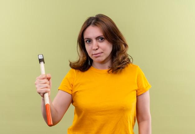 Giovane donna casuale sicura che tiene martello su spazio verde isolato