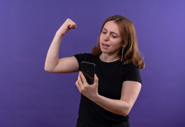 자신감이 젊은 캐주얼 여성 휴대 전화를 들고 복사 공간이 격리 된 보라색 공간에 휴대 전화를보고 강한 제스처를하고