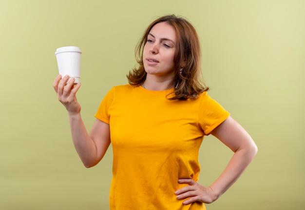 孤立した緑の空間で腰に手でプラスチックコーヒーカップを保持している自信を持って若いカジュアルな女性