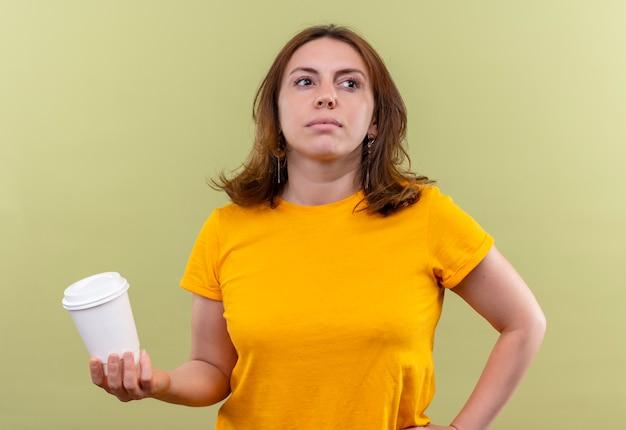 Giovane donna casuale sicura che tiene la tazza di caffè di plastica con la mano sulla vita su spazio verde isolato