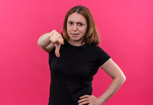 コピースペースと孤立したピンクのスペースに腰に手を指して自信を持って若いカジュアルな女性