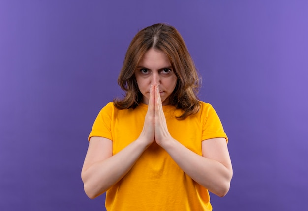 Уверенная молодая случайная женщина, сложив руки в жесте молитвы на изолированном фиолетовом пространстве с копией пространства