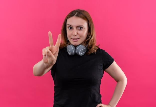 격리 된 분홍색 공간에 평화 서명을하고 목에 헤드폰을 착용하는 자신감이 젊은 캐주얼 여성