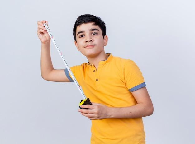 コピースペースで白い背景に孤立してまっすぐに見える巻尺を保持している自信を持って若い白人少年