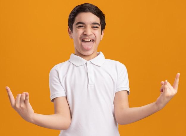Уверенный молодой кавказский мальчик показывает язык, делая знак рок