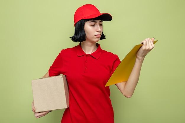 Fiduciosa giovane ragazza delle consegne caucasica che tiene in mano una scatola di cartone e guarda gli appunti