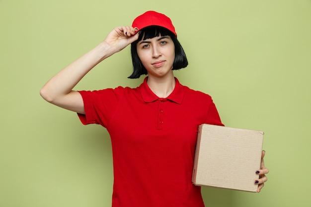Fiduciosa giovane ragazza caucasica delle consegne che tiene in mano una scatola di cartone e