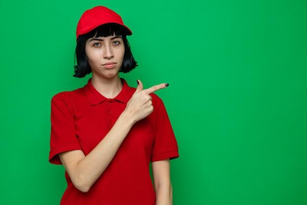 Fiducioso giovane caucasica ragazza delle consegne che punta a lato Foto Gratuite
