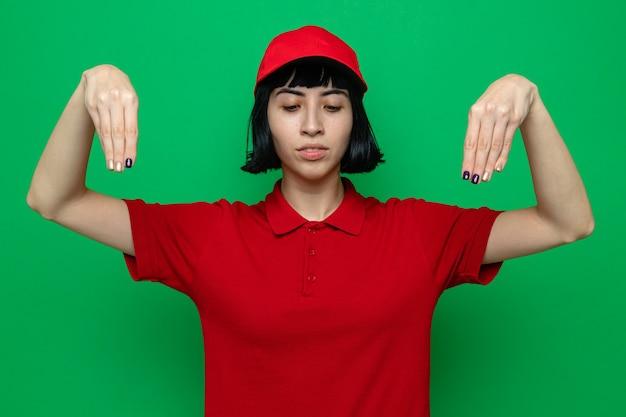 Fiduciosa giovane ragazza delle consegne caucasica che finge di tenere qualcosa e guarda in basso Foto Gratuite