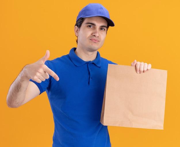 파란색 유니폼을 입고 모자를 들고 주황색 벽에 격리된 종이 패키지를 가리키는 자신감 있는 젊은 백인 배달원