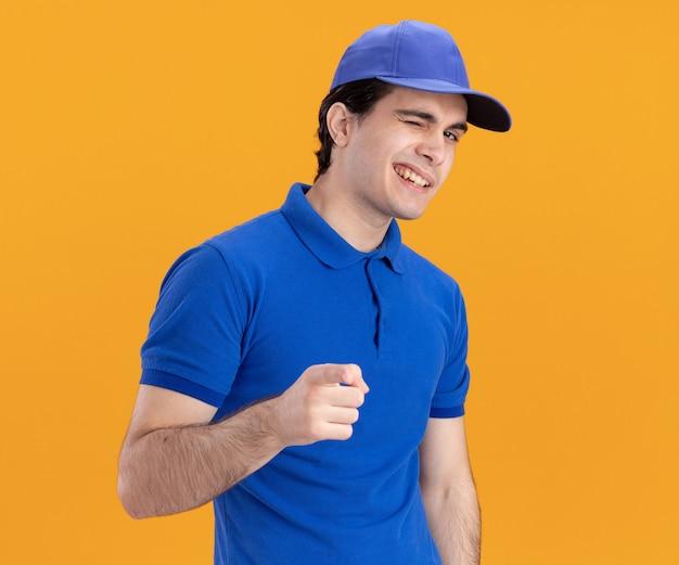 파란색 유니폼을 입은 자신감 넘치는 백인 배달원, 모자 윙크를 하고 주황색 배경에 놓인 카메라를 가리키며