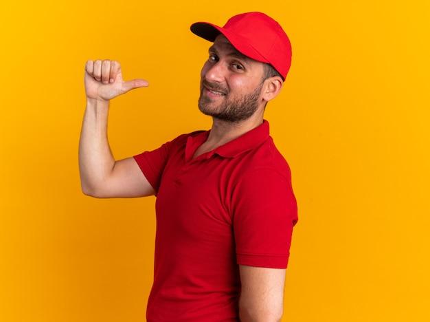빨간 제복을 입은 자신감 있는 백인 배달원과 프로필 보기에 서 있는 모자는 복사 공간이 있는 주황색 벽에 고립된 자신을 가리키는 카메라를 바라보고 있습니다.