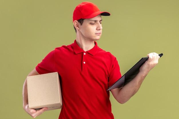 Fiducioso giovane fattorino caucasico in camicia rossa che tiene in mano una scatola di cartone e guarda gli appunti