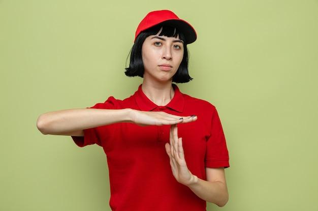 Fiduciosa giovane donna di consegna caucasica che gesturing segno di time out