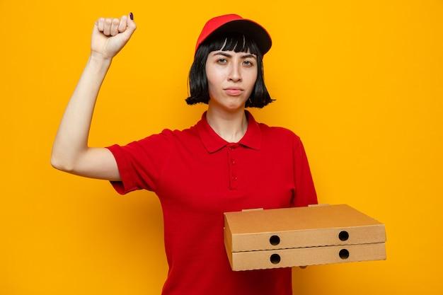 피자 상자를 들고 주먹을 들고 자신감이 젊은 백인 배달 여자