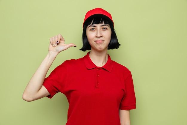 Fiduciosa giovane donna di consegna caucasica che indica se stessa
