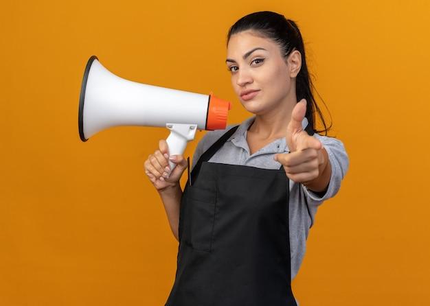 주황색 벽에 격리된 채 가리키는 스피커를 들고 제복을 입은 자신감 있는 젊은 백인 여성 이발사