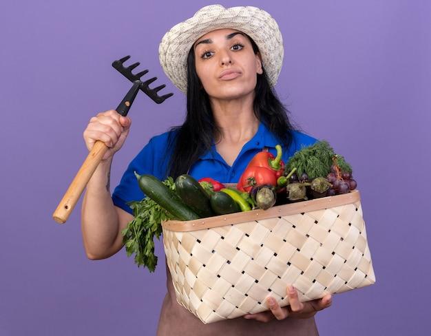 Fiducioso giovane giardiniere caucasica ragazza che indossa l'uniforme e cappello con cesto di verdure e rastrello