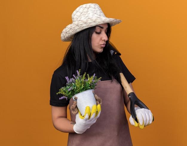 Fiducioso giovane giardiniere caucasica ragazza che indossa uniforme e cappello con guanti da giardiniere che tengono vanga e vaso di fiori guardando in basso