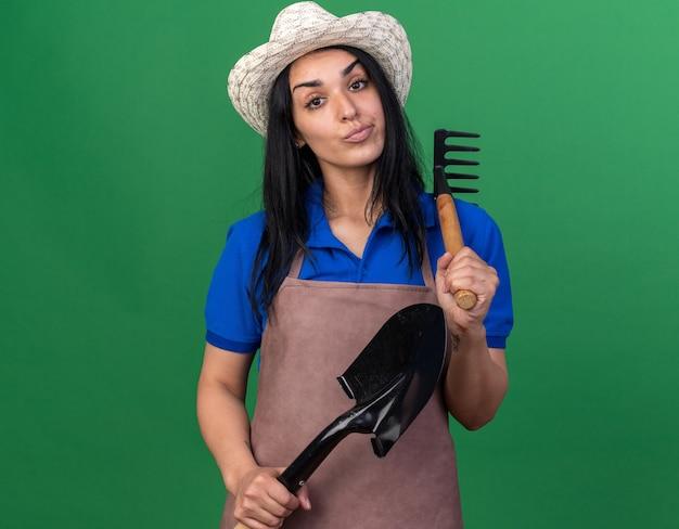 肩とスペードに熊手を保持している制服と帽子を身に着けている自信を持って若い白人の庭師の女性