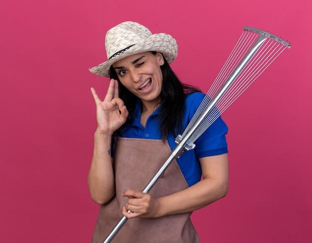 Fiducioso giovane giardiniere caucasica donna che indossa l'uniforme e cappello che tiene il rastrello delle foglie facendo segno ok strizzando l'occhio