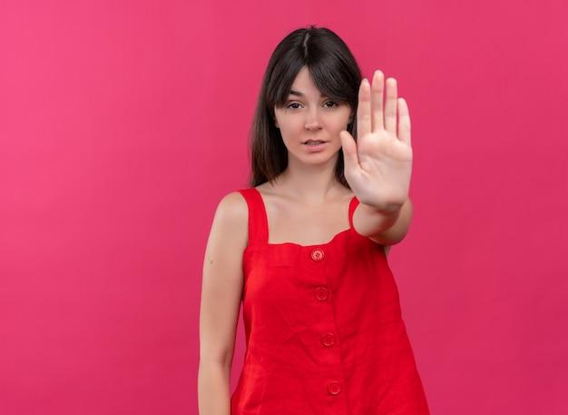 自信を持って若い白人の女の子はジェスチャーを停止し、コピースペースで孤立したピンクの背景にカメラを見ます