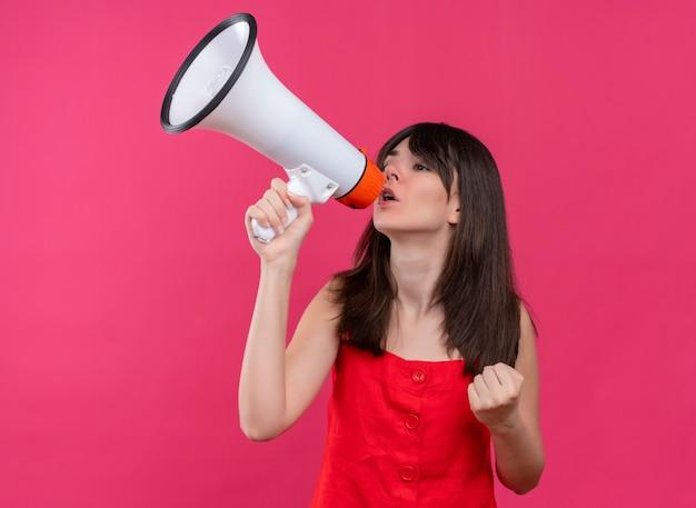 スピーカーを保持し、孤立したピンクの背景に拳を持ち上げて自信を持って若い白人の女の子