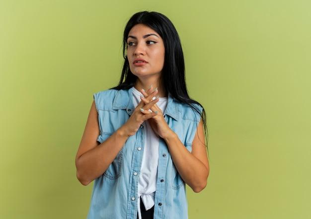 Fiduciosa giovane ragazza caucasica tiene le mani insieme guardando a lato