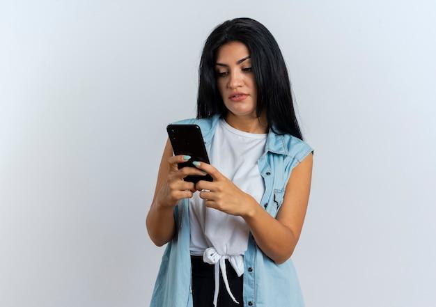 La giovane ragazza caucasica sicura tiene ed esamina il telefono