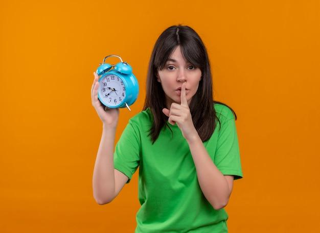 녹색 셔츠에 자신감이 젊은 백인 여자 시계를 보유하고 격리 된 오렌지 배경에 입에 손가락을 넣습니다