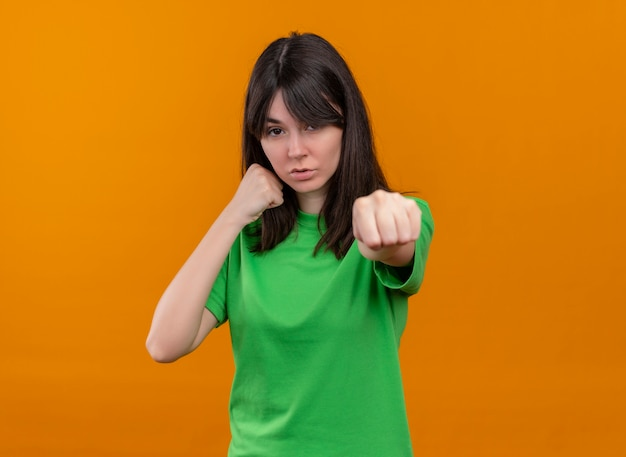 Уверенная молодая кавказская девушка в зеленой рубашке изображает удар на изолированном оранжевом фоне