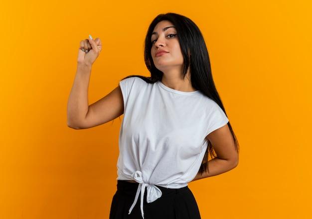 Fiduciosa giovane ragazza caucasica tiene il pugno e tiene la mano dietro