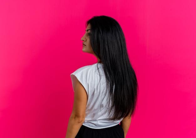 Fiduciosa giovane ragazza caucasica sta con la schiena alla telecamera guardando a lato Foto Gratuite