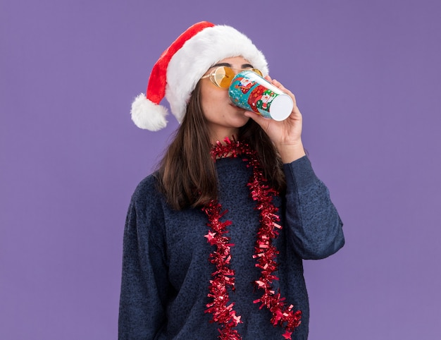 Confident young caucasian girl in sun glasses with santa hat and garland around neck drinks from paper cup isolated on purple background with copy space