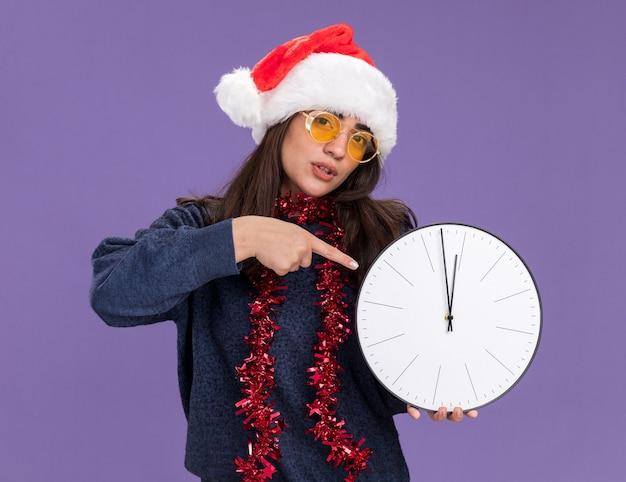 Fiduciosa giovane ragazza caucasica in occhiali da sole con santa cappello e ghirlanda intorno al collo tiene e indica l'orologio isolato su sfondo viola con spazio di copia
