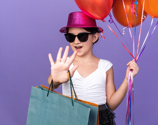 Confident young caucasian girl in sun glasses with violet party hat holding helium balloons and shopping bags gesturing stop sign isolated on purple wall with copy space