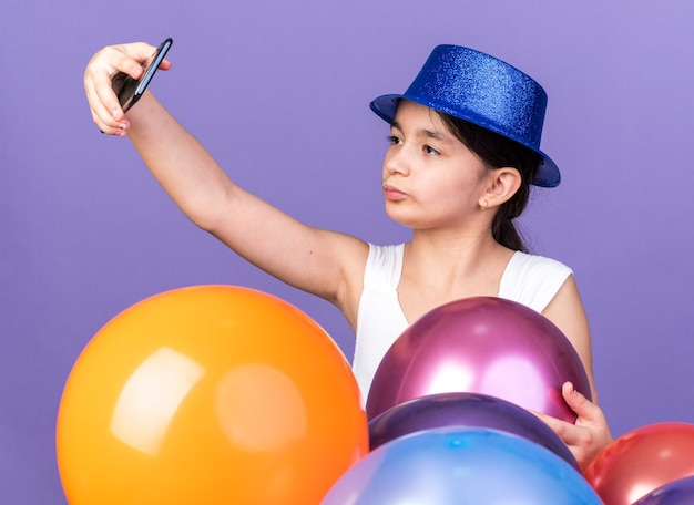 Confident young caucasian girl wearing blue party hat taking selfie on phone standing with helium balloons isolated on purple wall with copy space