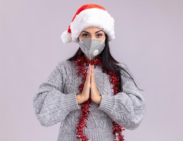 クリスマスの帽子と首の周りに見掛け倒しの花輪を身に着けている自信を持って若い白人の女の子は、白い背景で手を一緒に隔離してカメラを見て保護マスクを見て